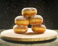 Стог donuts на фоне порошка сахара замороженности Стоковое Изображение RF