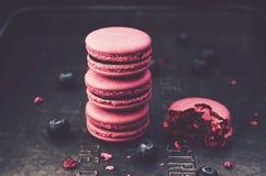 Стог macaroons и свежих ягод на темной предпосылке металла Стоковые Изображения
