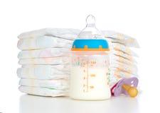 Стог soother ниппели пеленок и бутылки младенца подавая с mil Стоковое Фото