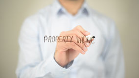 Стоимость имущества, сочинительство человека на прозрачном экране Стоковая Фотография RF