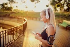 Стойка бегуна девушки в парке слушая к музыке Стоковое Фото