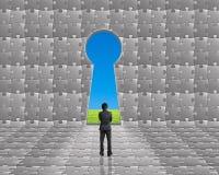 Стойка бизнесмена к двери формы отверстия для ключа на головоломках огораживает острословие Стоковое Фото