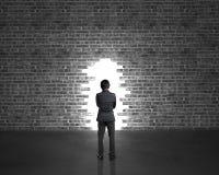 Стойка бизнесмена напротив большого отверстия на стене кирпичей в темном pl Стоковые Изображения RF
