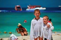 Стойка 2 братьев обнимая на пляже рая Дети одеты в рубашках для того чтобы защитить от ультрафиолетового луча Счастливые усмехаяс Стоковые Фото