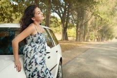 Стойка девушки на проселочной дороге около автомобиля, больших высоких деревьев, сезона лета Стоковое Изображение