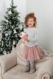 Стойка девушки ребенка около рождественской елки Стоковое Изображение