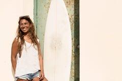 Стойка девушки с surfboard перед дверью grunge Стоковое фото RF