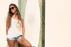 Стойка девушки с surfboard перед дверью grunge Стоковое Фото