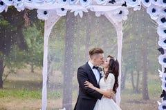 Стойка жениха и невеста около свода на свадебной церемонии Стоковое Изображение