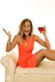 Стойка женщины в красном цвете сидит с стеклянное счастливым стоковая фотография rf