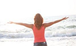 Стойка женщины на пляже с оружиями раскрывает Стоковые Фото