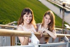 Стойка 2 жизнерадостная девушек на лестницах Стоковая Фотография RF