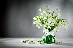 Стойка лилии Loddon белых цветков в стеклянной вазе на белых деревянных досках на серой предпосылке Стоковое Изображение