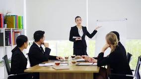 Стойка коммерсантки и представлять к коллегам в конференц-зале стоковая фотография rf
