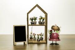 Стойка куклы девушки около цветков на рамке дома полки с пустой черной доской Стоковые Изображения RF