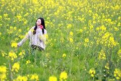 Стойка молодой женщины в середине желтых хранят цветков Коул, который Стоковые Фото