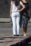 Стойка 2 молодых женщин на голубых джинсах перехода стоковые фотографии rf
