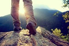 Стойка ног Hiker на утесе горного пика Стоковое Изображение RF