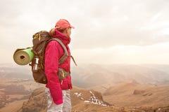 Стойка путешественника девушки утес высокий в горах Кавказа против фона заходящего солнца утесов и Стоковое Изображение