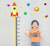 Стойка ребенк крупного плана счастливая азиатская для высоты измерения с милым шаржем на мраморной каменной стене текстурировала  стоковые фото