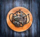 Стойка утюга года сбора винограда в форме бака чая на доске круга и голубой деревянной предпосылке, концепции чая Стоковые Изображения RF