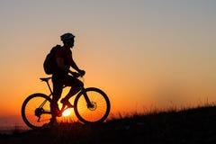 Стойка человека силуэта с горным велосипедом на луге Стоковая Фотография