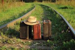 Стойка чемоданов старая на железнодорожных trackssuitcases старых на железнодорожных путях Стоковые Фотографии RF