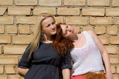 Стойка 2 девушок на стене Стоковые Изображения RF