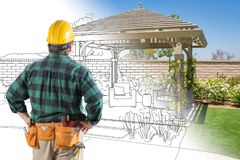 Стойки подрядчика смотря чертеж дизайна перголы патио и стоковая фотография