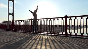 Стойки человека, дышают глубоко, поднимают руки, на заходе солнца на речном береге в Slo-Mo сток-видео