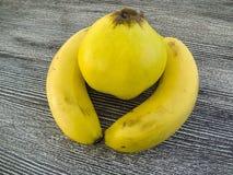 стойки bQuince в середине банана приносить, банан стоя на деревянном поле в интересных путях Стоковая Фотография RF