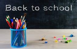 Стойте для ручки и карандашей и красочных бумажных зажимов на деревянной плате Стоковое Изображение RF