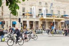 СТОКГОЛЬМ, ШВЕЦИЯ - 28-ОЕ МАЯ 2016: Взгляд улицы с пешеходами и велосипедистами Королевский драматический театр на заднем плане стоковое фото rf