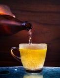 Сток пива лагера от бутылки к стеклу на таблице с деревянной пользой предпосылки для напитка спирта выпивая в взрослых пабе, баре Стоковое фото RF
