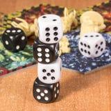 Столбец кости на предпосылке объектов для игр таблицы на поверхности деревянного стола Стоковое фото RF