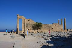 Столбцы на эллинистическом stoa акрополя Lindos, Родоса, Греции, голубого неба, оливкового дерева и красивого вида на море в задн Стоковое фото RF