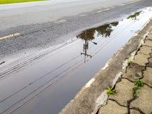 Столб и линия электричества отражают на вод-внесенное в журнал на улице стоковое фото rf