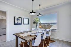 Столовая с белыми стенами и деревянным столом стоковые фотографии rf