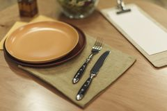 Столовый прибор, пустые плиты и салфетки на деревянной столешнице Стоковые Фотографии RF