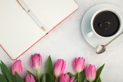Стол женщины работая с кружкой кофе, тетрадью и тюльпаном весны цветет взгляд сверху в стиле положения квартиры Взгляд сверху с к Стоковое Фото