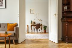Стол и стул в интерьере домашнего офиса Взгляд через дверь винтажной живущей комнаты Реальное фото стоковая фотография