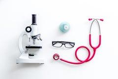 Стол лаборатории со стетоскопом, таблетки в пробирке и микроскоп на белом взгляде сверху предпосылки стоковые изображения