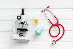 Стол лаборатории со стетоскопом, таблетки в пробирке и микроскоп на белом деревянном взгляде сверху предпосылки стоковые изображения