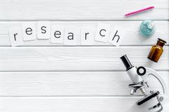 Стол лаборатории с текстом исследования, таблетки в пробирке и микроскоп на белом деревянном космосе взгляда сверху предпосылки д стоковая фотография