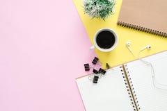 Стол офиса взгляд сверху с тетрадями, заводом, кофейной чашкой, наушником и космосом экземпляра на предпосылке пастельного цвета стоковая фотография