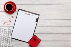 Стол офиса мыши клавиатуры бумажных зажимов часов чашки кофе тетради белой папки доск таблицы красный Стоковое Фото
