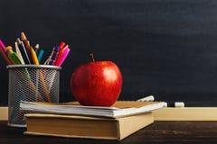 Стол учителя с материалами сочинительства, книгой и яблоком, пробелом для текста или предпосылкой для темы школы скопируйте космо стоковые изображения