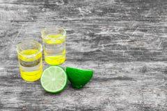 Стопки с золотой мексиканской текила с кусками известки и солью на старом деревянном столе Селективный фокус Традиционное мексика Стоковое фото RF