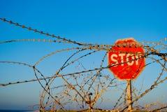 Стоп дорожного знака стоя на солнце лета голубого неба моря загородки загородки колючей проволоки пляжа стоковое изображение