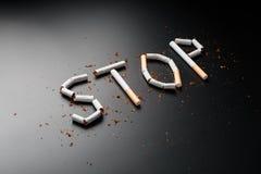 СТОП надписи от сигарет на черной предпосылке Остановите курить Концепция куря убийств Надпись мотивации к стоковые изображения